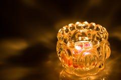 Close up of shot burning candle. Close up shot burning candle inside glass jar  on black background Royalty Free Stock Images