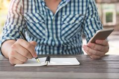 Close up shot business man taking down note writing with ballpoi Royalty Free Stock Image