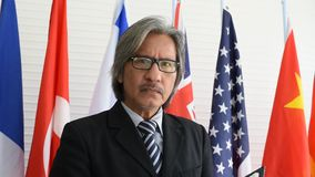 Close up shot of business or political man feel upset and stand in front of international flags stock footage