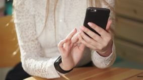 Close up shot of business woman`s hands, who checks news on the smartphone. stock footage