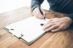 Close-up of businessman signing contract or document on wooden desk stock photo