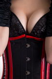 Close-up shot of busty fetish woman in corset and bra Stock Photos