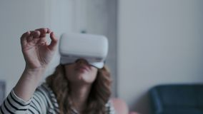 Close-up shot. Camera moves around young girl wearing mobile virtual reality glasses. She trying to catch and touch stock footage