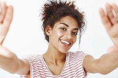 Close-up shot of carefree friendly dark-skinned woman, pulling hands towards camera as if making selfie, smiling broadly royalty free stock image