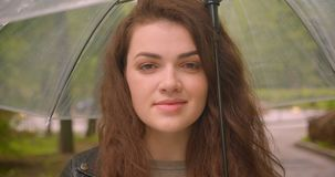 Close-up shot of caucasian brunette female under umbrella smiles prettily and calmly into camera in the green city park. Close-up shot of caucasian brunette stock video footage