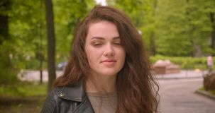 Close-up shot of caucasian brunette female watches into camera with calm smile in the green city park. Close-up shot of caucasian brunette female watches into stock video footage