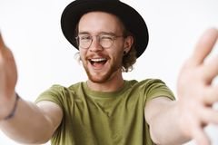 Close-up shot of charismatic and flirty young male romantic with beard and pierced nose in hat and glasses winking and royalty free stock photos