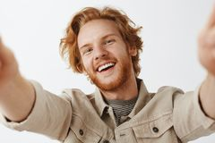 Close-up shot of charming friendly and carefree happy redhead guy with stylish wavy hairstyle and beard tilting from joy. Smiling, pulling hands towards camera stock image
