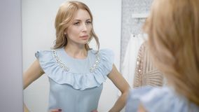 Close up shot of a charming woman trying on a new blue dress. She is standing in front of mirror in changing room. Likes the look stock video footage