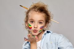Beautiful little girl with a painted hands and cheeks is posing on a gray background. Close-up shot of a cheerful girl with a painted cheeks having a brush in stock photo