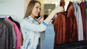 Close-up shot of a cheerful young woman chatting on mobile phone and shopping for clothes in women`s clothing store. She. Is checking price and quality of coat stock video