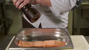 Close up shot of the chef`s hands, who sprinkles salt with a piece of trout. Close up shot of the chef`s hands, the man holds a pepper, with which he sprinkles stock video footage