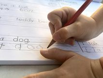 Close-up shot of child hands writing in the book Royalty Free Stock Photo