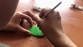Close-up shot of a child painting a small wooden cut in green color. Handicraft activity.  stock video