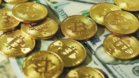 Glimmering golden coins with bitcoin symbol. Close-up shot of composed gold physical bitcoins on top of various dollar banknotes in light stock video footage