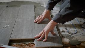 Close up shot of a construction worker laying ceramic tile on the levelled floor in the flat. stock video