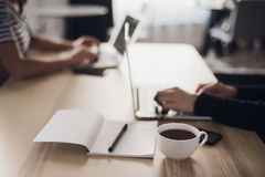 Close up shot of a cup of coffee, notebook with pencil or pen and hands typing on keyboard of a laptop. stock photo