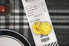 Paying with Bitcoin or other crypto currency at a restaurant stock photography