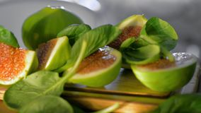 Basil leaves falling on cut green figs. Close-up shot of cut green figs on wooden board with falling fresh basil leaves stock footage
