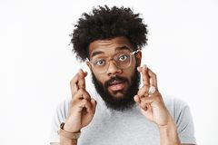 Close-up shot of cute african american adult bearded guy with afro hairstyle and pierced nose in glasses crossing hands royalty free stock photos
