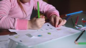 Close-up shot of cute Caucasian little girl learning to draw on paper holding a pencil with whole hand at home table. stock video