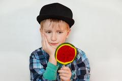 Close up shot of cute little boy holding big lollipop in his hand holding his other hand on cheek looking at candy with great desi Royalty Free Stock Photography