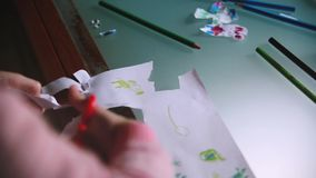 Close-up shot of cute little girl`s hands cutting handdrawn pictures out from a paper sheet with scissors at a table. Happy focused female elementary kid stock video
