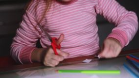 Close-up shot of cute little girl`s hands in pink sweater cutting paper shapes with scissors and drawing with a pencil. Happy focused female elementary kid stock footage