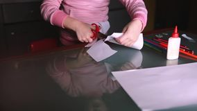 Close-up shot of cute preschool girl in pink sweater cutting shapes with scissors from paper, reflecting in glass table. stock footage