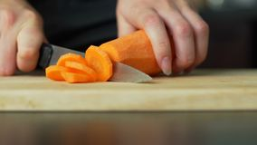 Woman cutting the carrot. Close-up shot of cutting the carrot in slow motion stock footage