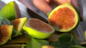 Cut green figs and basil leaves. Close-up shot of cutting green fig on wooden board with basil leaves. View to fruit cut in warm sunlight stock footage