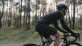 Close up shot of cyclist pedaling bike wearing black jersey, shorts, helmet and sunglasses. Back road carbon bicycle in the park. Slow motion stock footage