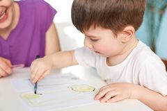 Close up shot of dark haired handsome male kid being focused at paper with picture, draws with great desire, unrecognizable female. Sits next to him, helps to Royalty Free Stock Photos