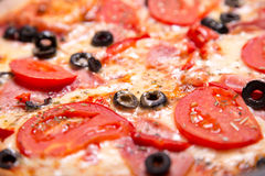 Close-up shot of delicious Italian pizza with ham, tomatoes and Royalty Free Stock Image