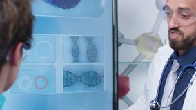Close up shot of doctor and nurse looking at monitor with DNA sample. In modern laboratory stock footage