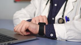 Close up shot of the doctor`s hand, who uses a smart watch to check a mail stock video