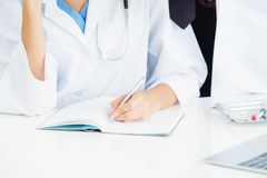 Close up shot of doctor writing report. Close up shot of doctor writing on notebook report at the office in hospital. Healthcare professional stock photos