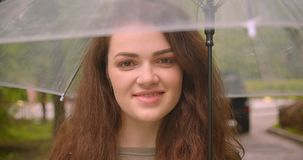 Close-up shot of dreamy caucasian brunette model with umbrella smiles shyly and prettily into camera in the green rainy. Park stock video footage