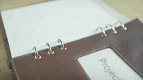 Close up shot elegant business project note pad book daily planner bullet journal in brown leather case on wooden table. Close up shot of elegant business stock video footage