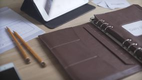 Close up shot of elegant light brown leather case note pad book daily planner bullet journal habit tracker on wood table. Close up shot of elegant business light stock footage