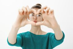 Close-up shot of emotive cute caucasian woman in glasses, pulling hands towards camera and zoom on heart gesture, gazing royalty free stock images