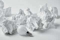 Close-up shot of energy saving light bulb with crumpled papers. On white royalty free stock image