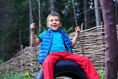 Broad smiling little boy sitting on tire swing. Close-up shot of excited boy sitting on tire swing at playground Royalty Free Stock Photos