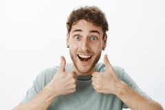 Close-up shot of excited happy fair-haired boyfriend in earrings and bristle, saying yeah and showing thumbs up, smiling stock photography