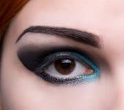 Close-up shot of an eye with artistic makeup. Close-up shot of an eye with artistic blue and black makeup royalty free stock photo