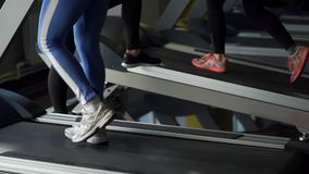 Close up shot of the feet of women who walk on the treadmill during training stock video footage