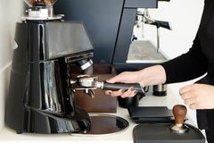 Close up shot of female barista in process of making coffee beverage. royalty free stock photography