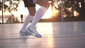 Close up shot of female basketball player legs doing dribbling exersice very quickly without ball, training outdoors on stock footage