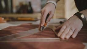 Close-up shot of female hands cutting a big piece of leather on a workshop table with knife and triangular curve ruler. Detailed process of making quality stock video