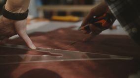 Close-up shot of female hands cutting pieces out of leather on big workshop table with knife and triangular curve ruler. Close-up shot of skilled professional stock footage